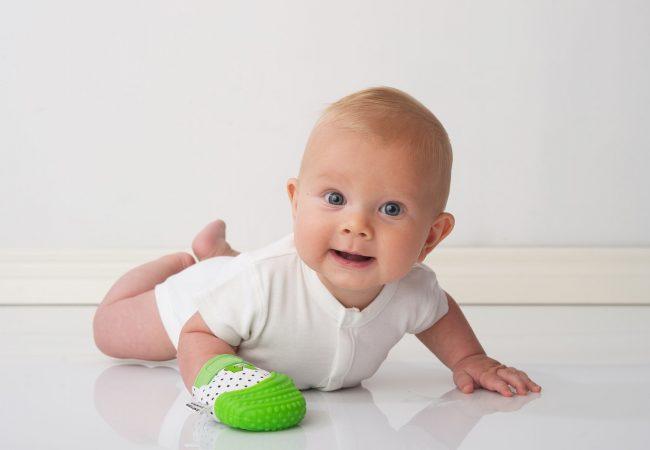 Bébé-a-plat-ventre-avec-mitaine-de-dentition-verte