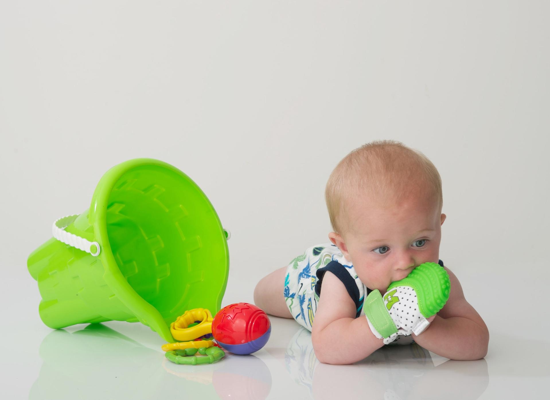bébé-avec-ses-jouets-et-sa-mitaine-de-dentition